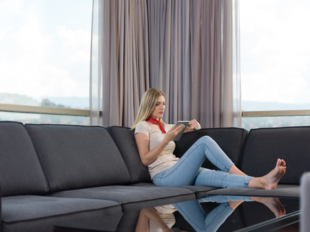 beautiful young woman on sofa at home surfing  internet using tablet computer