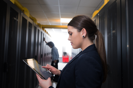 Female IT engineer working on a tablet computer in server room at modern data center Archivio Fotografico
