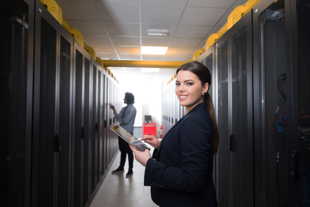 Ingeniero informático de sexo femenino que trabaja en una tableta en sala de servidores en el centro de datos moderno