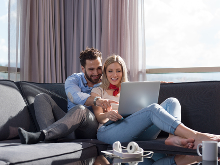 Young couple relaxing at luxury home using laptop computer reading in the living room on the sofa couch. 版權商用圖片