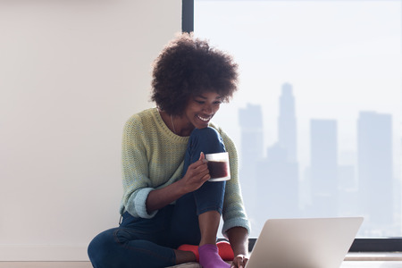 Young african american woman smiling sitting on the floor near bright window while looking at open laptop computer and holding mug at home Stock Photo