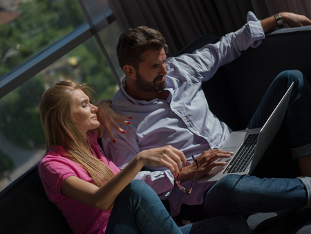 Young couple relaxing at luxury home using laptop computer reading in the living room on the sofa couch. Stock Photo