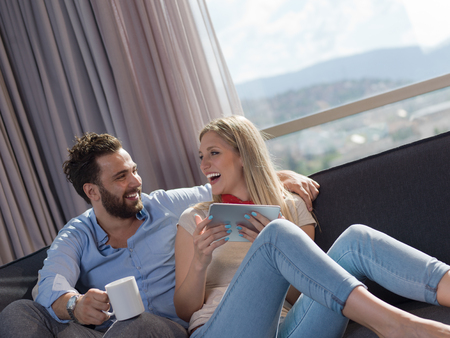 Young couple relaxing at  home using tablet computers reading in the living room on the sofa couch. Stock Photo