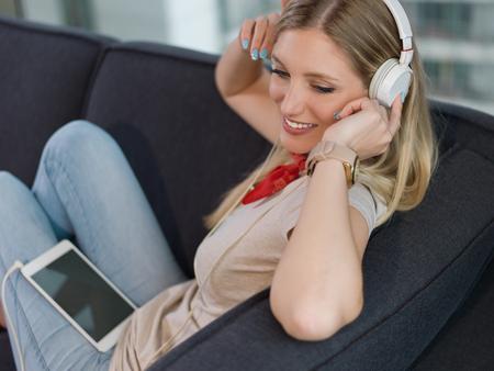 Young beautiful girl enjoying music through headphones, laying on sofa at home Stock Photo