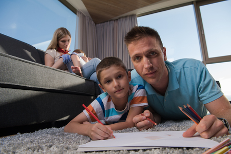 Happy Young Family Playing Together at home on the floor using a tablet and a childrens drawing set Stockfoto