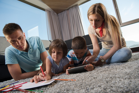 Happy Young Family Playing Together at home on the floor using a tablet and a childrens drawing set Imagens