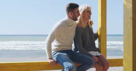 Happy couple enyojing time together on beach during autumn day Stock Photo