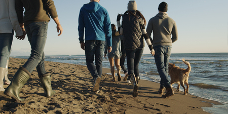 Group Of Young Friends Spending The Day On A Beach during autumn day Stock Photo