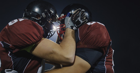 American Football Players having fun and knocking each other with helmet