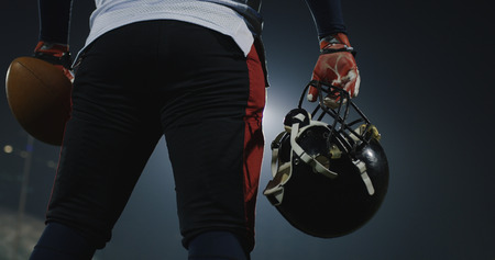 portrait of American Football player holding ball and helmet  rear view