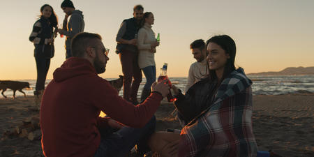 Happy Carefree Young Friends Having Fun And Drinking Beer By Bonefire On The Beach As The Sun Begins To Set Reklamní fotografie