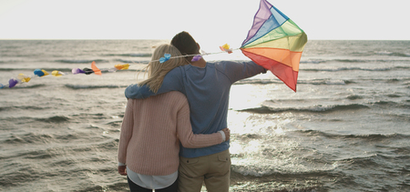 Loving Couple Flying A Kite at Beach and having fun on autumn day
