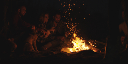 Young Couple Sitting with friends Around Campfire on The Beach At Night drinking beer Фото со стока