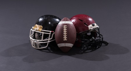 american football and helmets isolated on gray background