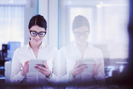 Jolie femme d & # 39 ; affaires en utilisant la tablette en utilisant un intérieur de bureau de démarrage Banque d'images - 98355305