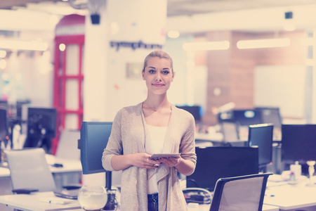 Jolie femme d & # 39 ; affaires en utilisant la tablette en utilisant un intérieur de bureau de démarrage Banque d'images - 98381511