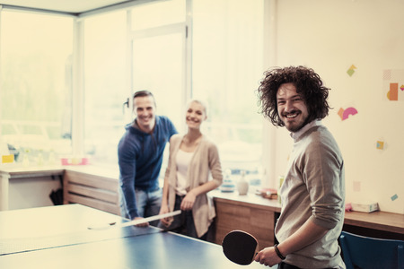 group of young startup business people playing   table tennis at modern creative office