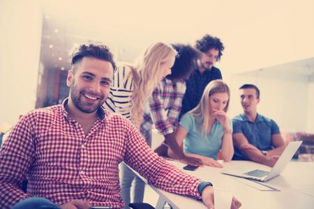 オフィスで同僚をバックに微笑む若い非公式のビジネスマンの肖像画 写真素材