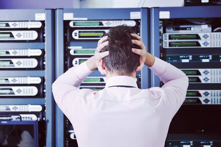 L & # 39 ; homme d & # 39 ; affaires dans la salle de serveur réseau ayant des problèmes et de prendre la crise de la machine de Banque d'images - 98402353