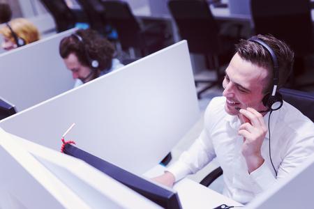 jeune opérateur mâle sourire opérateur de travail faisant son travail avec un casque Banque d'images
