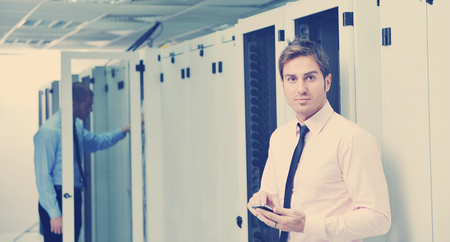 young business man computer science engeneer talking by cellphone at network datacenter server room asking  for help and fast solutions and services Stock Photo