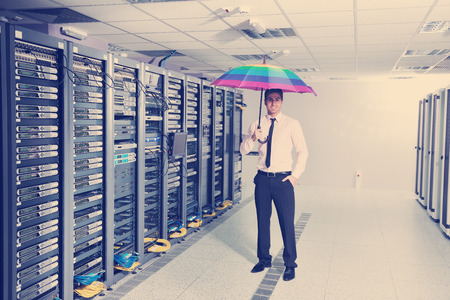 young handsome business man  engineer in  businessman hold  rainbow colored umbrella in server datacenter room  and representing security and antivirus sofware protection concept Stock Photo
