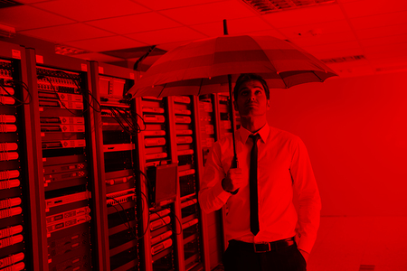young handsome business man  engineer in  businessman hold  rainbow colored umbrella in server datacenter room  and representing security and antivirus sofware protection concept Фото со стока
