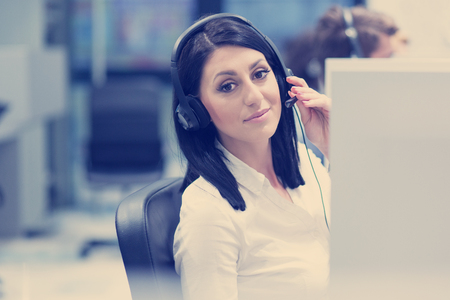 young smiling female call centre operator doing her job with a headset Foto de archivo