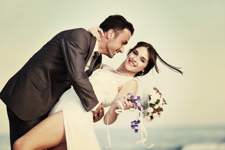 happy just married young couple celebrating and have fun at beautiful beach sunset Stockfoto