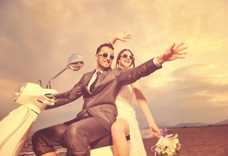 sposi di sposi appena sposati sulla spiaggia cavalcare scooter bianco e divertirsi