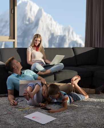 Happy Young Family Playing Together at home on the floor using a laptop computer and a childrens drawing set