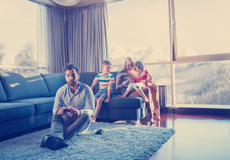 Happy family. Father, mother and children playing a video game Father and son playing video games together on the floor Stock Photo