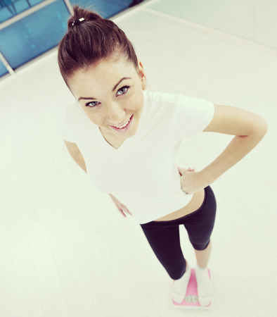 happy diet concept with young woman on pink scale at sport fitnes gym club
