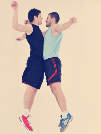 two young adults exercise fitness jumping and relaxing at sport gym club