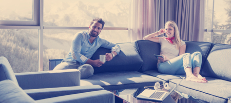 Young couple relaxing at  home using tablet computer reading in the living room near the window on the sofa couch. Stock Photo