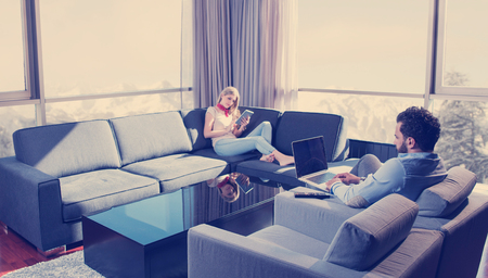 Young couple relaxing at home using tablet and laptop computers reading near the window on the sofa couch.