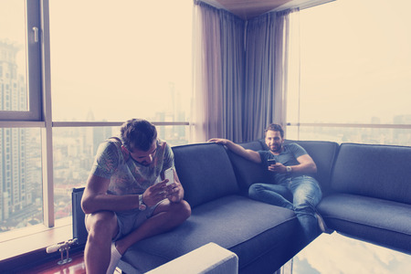 Handsome casual young men using a mobile phones  near the window at home Stock Photo