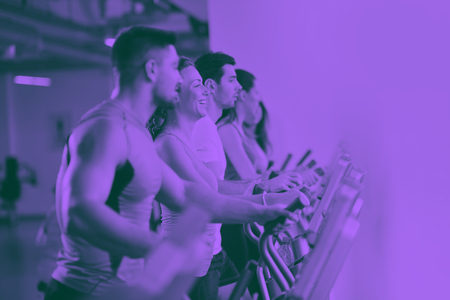 group of young people running on treadmills in modern sport  gym duo tone