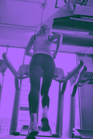 sport, fitness, lifestyle, technology and people concept - smiling woman exercising on treadmill in gym duo tone Stock Photo