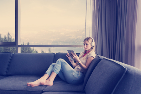 Young beautiful girl enjoying music through headphones, laying on sofa near the window at home