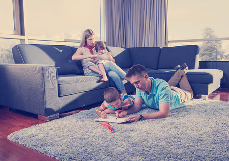 Happy Young Family Playing Together at home on the floor using a tablet and a childrens drawing set Stock Photo