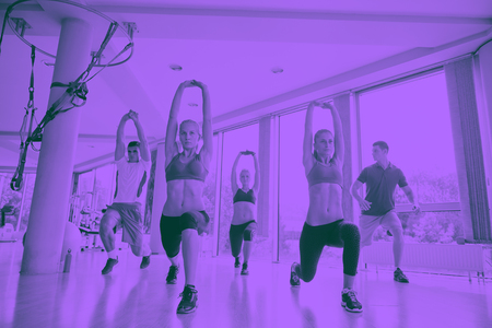 group of young people working out in a fitness gym duo tone Stock Photo