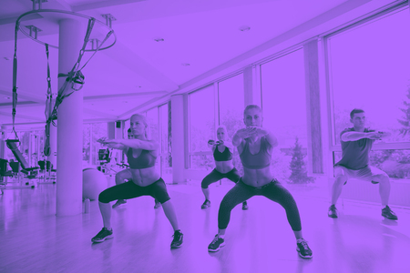 group of young people working out in a fitness gym duo tone Reklamní fotografie
