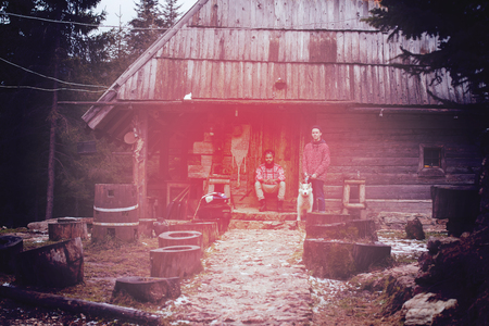 hipsters couple portrait, two young  man with white husky dog  sitting in front of old wooden retro house 版權商用圖片