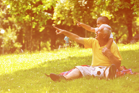 happy grandfather and child have fun and play in park Stock Photo