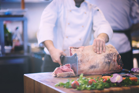 chef using ax while cutting big piece of beef  on wooden board in restaurant kitchen 版權商用圖片