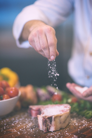 Master Chef hands putting salt on juicy slice of raw steak with vegetables around on a wooden table