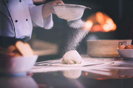 chef sprinkling flour over fresh pizza dough on kitchen table Stockfoto