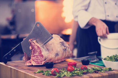chef using ax while cutting big piece of beef  on wooden board in restaurant kitchen 스톡 콘텐츠