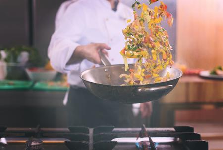 Giovane cuoco unico maschio che lancia le verdure nel wok alla cucina commerciale Archivio Fotografico